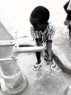 child at water pump